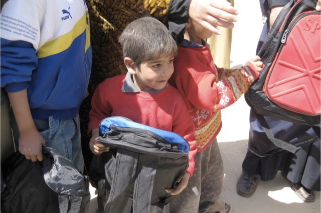 """A young Iraqi boy holds a backpack distributed by Soldiers from Company A, 2nd Battalion, 35th Infantry Regiment, 3rd Infantry Brigade Combat Team, 25th Infantry Division.  The backpack was donated by the Hyde family of Modesto, Calif. 1st Lt. Daniel Hyde was killed in action March 7 by insurgent attack in Samarra. """""""