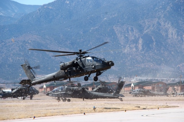 FORT CARSON, Colo.-An AH-64 Apache attack helicopter with the 1st Battalion, 2nd Aviation Regiment, 2nd Infantry Division, prepares to land at Fort Carson's Butts Army Airfield April 6 while others await refueling. Twelve of the 1-2nd AVN's 24 Apaches arrived at Fort Carson as part of the unit's restationing to the Mountain Post from Camp Eagle, Wonju, Republic of Korea. When the move is complete, the unit will bring about 350 Soldiers and 100 contractors to Fort Carson.