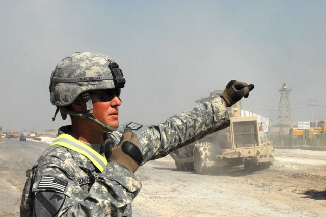 VICTORY BASE COMPLEX, Iraq - San Antonio native, Sgt. James Bartholomae, 227th Engineer Company, directs traffic on Western Bypass road, here, April 6.  He heads a team of engineers responsible for laying down a better foundation for the road.