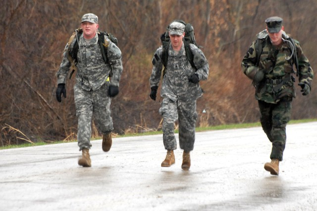 Sgt. John Lennon, Staff Sgt. John Brisbane and Navy Petty Officer John Pugh march through rain and mud around Sherman Army Airfield April 2 during the last event for the German Armed Forces Badge for Military Proficiency ay Fort Leavenworth, Kan.