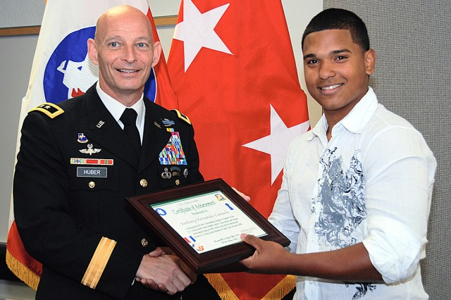 Maj. Gen. Keith Huber, commander of U. S. Army South, presents a certificate of achievement to Cole High School sophomore Anthony Hernandez-Camacho March 31. Hernandez-Camacho drew the winning design for the Army South Fiesta medal.
