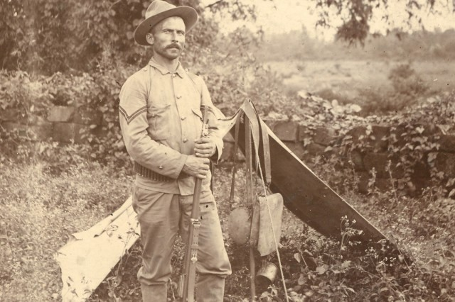 """Image shows Private George Tranz of Company """"K"""", of the 3rd Infantry Regiment. He is standing beside his tent while serving in the Philippine Islands in the early 1900's. (Spanish-American War Survey Photograph Collection)."""