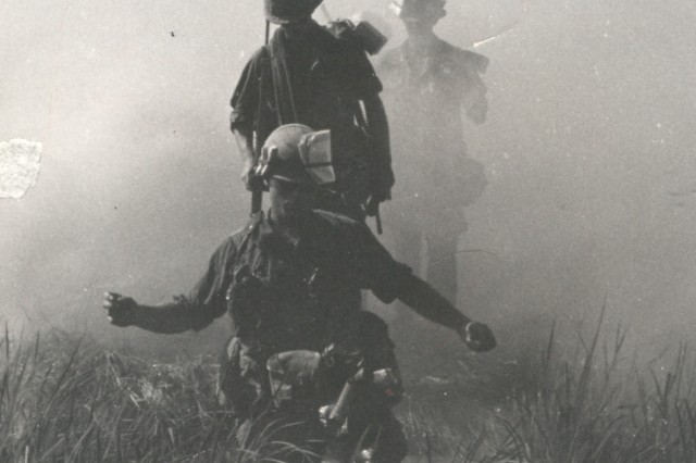 """Out of the Mist. Captain William H. Denny, Jr. (Moorefield, WV) commanding officer, Company """"D,"""" 2nd Battalion, 3rd Infantry Regiment, 199th Light Infantry Brigade is shown leading his command group across a small rice paddy duirng opertions near Binh Chanh, ten miles south of Saigon. He is followed by his radio opertor, Specialist Four Peter Battin (Huntington, NY), November, 1968. (Vietnam Miscellaneous Photograph collection)."""