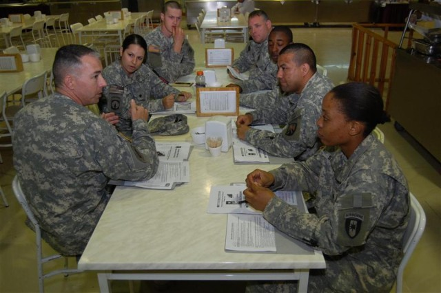 Chief Warrant Officer 3 Jeffrey White, a Durbin, W.Va., native and electronic maintenance warrant officer, 16th Sustainment Brigade, discusses the criteria for becoming a warrant officer with Staff Sgt. Amencio Almanza (second from left), night battle noncommissioned officer, 16th Special Troops Battalion, 16th Sust. Bde., and other hopefuls, during a warrant officer recruitment symposium at the Knight's Feasting Hall dining facility at Contingency Operating Base Q-West, Iraq, March 21. White discusses eligibility criteria and vocational benefits to several Soldiers interested in electronics, military intelligence, and food service warrant officer positions. Warrant officers from nearly every field met with Soldiers during the symposium.