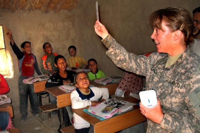 """Capt. Traci Earls, 287th Sustainment Brigade Support Operations Plans officer in charge, plays a game of flashcards with students at Al Soonobar Elementary School in Dhi Qar Province of Iraq, March 26. Earls spent the afternoon with the children as part of the  """"Read Iraq"""" initiative which brings Soldiers into classrooms to read to the children."""