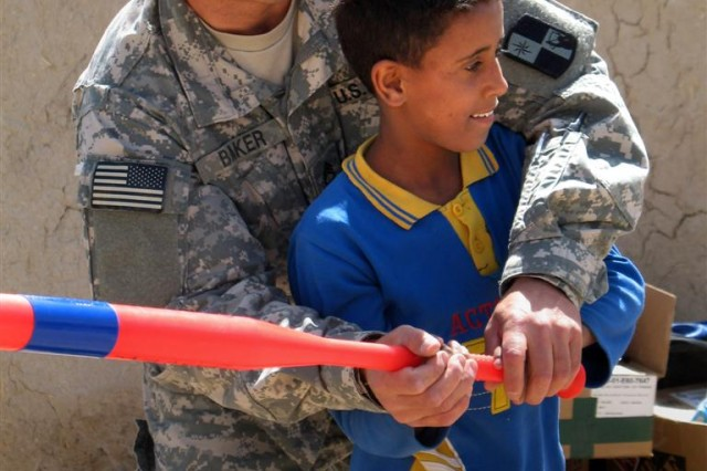 287th Sustainment Brigade Postal Supervisor, Sgt. 1st Class Chris Baker shows a student at Al Soonobar Elementary School how to swing a bat during his introduction to baseball.
