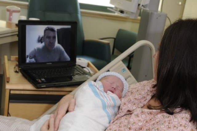 Lt. Col. James Baker uses the internet from COB Speicher, Iraq, to interact with his wife Amanda and their newborn son, Jesse James, shortly after he was born Feb. 13 in Florida. Using a popular video-teleconferencing program, Baker was able to be in the delivery room - virtually - as Amanda gave birth.