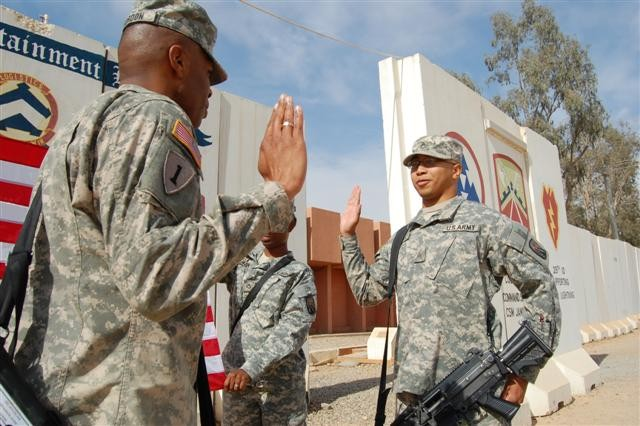 "Sgt. Carlos A. Santiago, a native of Fayetteville, N.C., re-enlists in front of the 16th Sustainment Brigade headquarters at Contingency Operating Base Q-West, Iraq, March 18. The ceremony was memorable because he was re-enlisting on his birthday and during the Army's ""Year of the NCO."" ""Re-enlisting during the 'Year of the NCO' is significant to me because the NCO is the backbone of the Army, providing motivation, purpose, and direction to the Soldier and guidance and support to the officer,"" Santiago said. ""Doing so on my birthday was just icing on the cake.  How many people can say they did that?"""