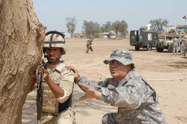 Staff Sgt. Javier Zapata (right), of York, Pa., a Soldier with Headquarters Company, 328th Brigade Support Battalion, 56th Stryker Brigade Combat Team, looks over a sector of fire with an Iraqi Army Soldier.