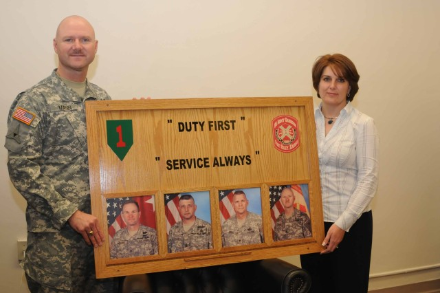 Garrison Command Sgt. Maj. Ian Mann and Customer Service Officer Michelle Simmons hold up a newly constructed command board, which will soon be hanging in a garrison organization on post to showcase its commitment to service.