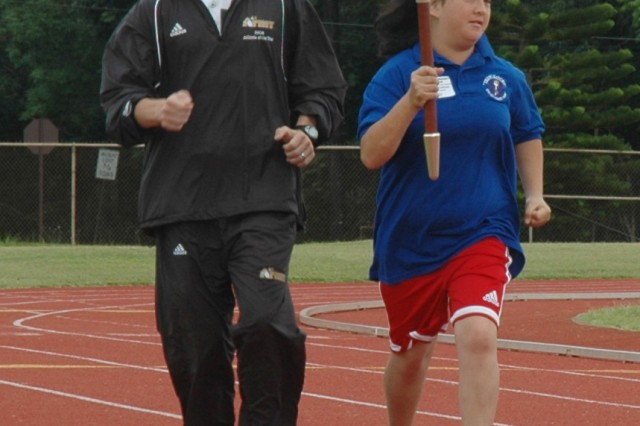 Jennifer Bowman runs with the torch alongside Army Athlete of the Year Capt. Shawn Dodge, 732nd Military Intelligence Battalion, to kick off the 2009 Special Olympics-Hawaii, Central Honolulu and Windward Track and Field Meet April 4 at Stoneman Stadium.
