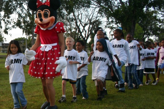 "SCHOFIELD BARRACKS, Hawaii - Minnie Mouse leads a march around the Bennett Youth Center Field, here, during the Child, Youth and School Services (CYS2) ""PT in the Park"" event, April 7. More than 157 children, ages 2-8, and more than 25 parents participated in the 30-minute ""mousercise"" aerobic routine with Mickey Mouse and friends. The annual event kicks off Month of the Military Child celebrations for U.S. Army Garrison-Hawaii."