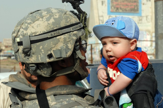 BAGHDAD - Pfc. Gbenga Ayantade, a combat medic from Chicago, assigned to the 1st Battalion, 5th Cavalry Regiment, gives an Iraqi baby a firsthand look at American hospitality April 9. Ayantade, who came to the U.S. in 2007 and is originally from Nigeria, helped keep the community safe by operating a checkpoint with Iraqi Security Forces during the sixth anniversary of the fall of Saddam Hussein.