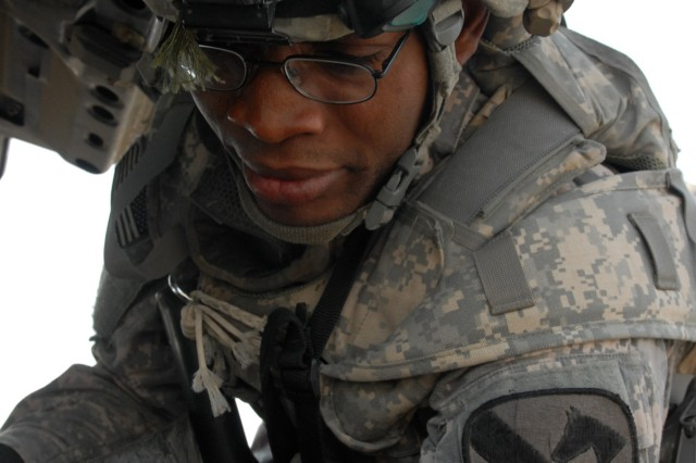 BAGHDAD - Chicago native, Pfc. Gbenga Ayantade, a combat medic assigned to the 1st Battalion, 5th Cavalry Regiment checks vehicles for improvised explosive device materials, unregistered weapons and anything else illegal during an operation April 9 in northeast Baghdad.
