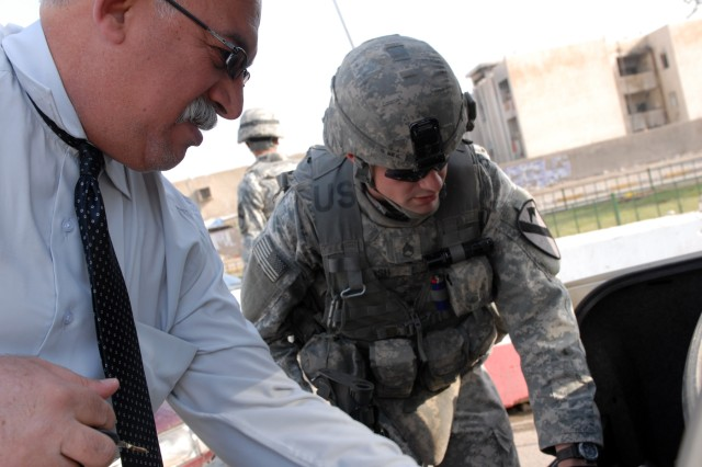 """BAGHDAD - Staff Sgt. Gerald Bush, an infantry squad leader from Holly Hill, S.C., assigned to the 1st Battalion, 5th Cavalry Regiment, checks the back of an Iraqi man's trunk an operation April 9 here. """"The whole entire city is a checkpoint today,"""" said Bush. """"We're looking for IED materials or anything illegal that can be transported."""" The mission succeeded in disrupting the movement of insurgents on a day that is historically bloody."""