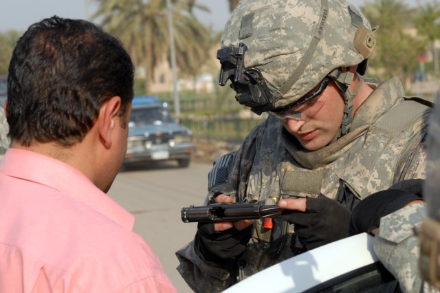 """BAGHDAD - An Iraqi man watches on as Cpl. Cameron McNeel, an infantry team leader from Houston assigned to 1st Battalion, 5th Cavalry Regiment,  checks the serial number on the man's handgun with the serial number on the man's weapon's registration card April 9 at a traffic control point here. """"I'd like to certainly be able to look at them and say, 'Hey this is for your safety and for the safety of the Iraqi people!' But I'm not that good at Arabic yet,"""" explained McNeel."""