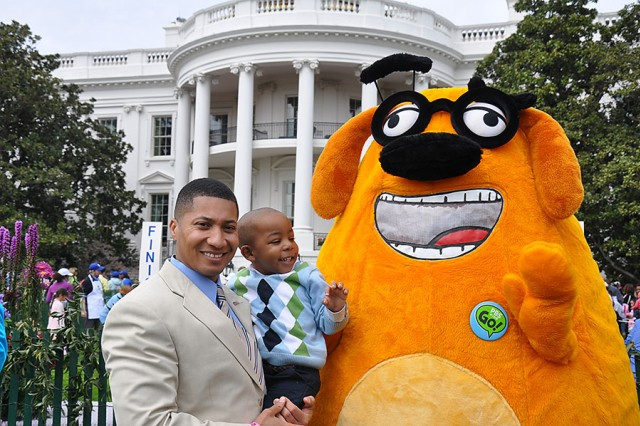 """Maj. Richard Harrison and his son from Fort Bragg, N.C., pose with PBS character """"Ruff Ruffman"""" in front of the White House Monday during the annual Easter Egg Roll."""