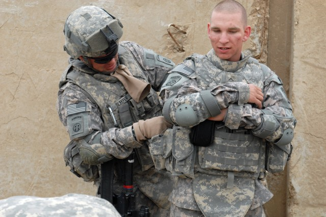 BAGHDAD - Detroit native Spc. Jason Sleeper (left), Company A, Brigade Support Battalion, 3rd Bde., 82nd Airborne Division, does pre-combat checks on Co. A Soldier, Pvt. Timothy Rickett, before a logistics mission, April 6. This is the first mission for Rickett, who hails from Cincinnati.