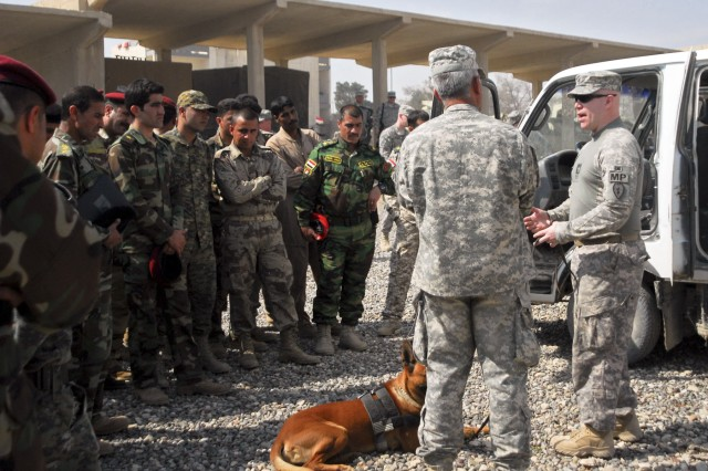 Staff Sgt. Michael Hile, a military working dog handler with the 527th Military Police Company, 709th Military Police Battalion, 18th Military Police Brigade, and a native of Prineville, Ore., explains the importance of the military working dog to the Iraqi Army soldiers, April 6, at Combat Outpost Spear in Mosul. Hile and his canine companion, Rronnie, demonstrated their skills in search, detain and attack for the Iraqi soldiers.