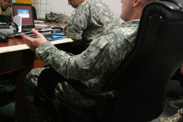 First Lt. Ty Roseberry, a physician assistant, medical platoon, 1st Battalion, 185th Armor, and Sgt. 1st Class Robert Tackett, medical platoon sergeant, discusses the new emergency medical information during weekly refresher training at Contingency Operating Base Speicher, Iraq, March 28.