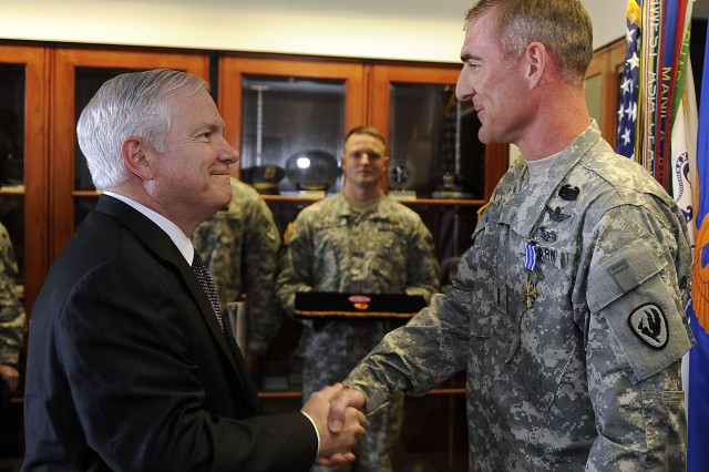 Defense Secretary Robert M. Gates congratulates Chief Warrant Officer 4 Paul F. Druse, Jr. on receiving the Distinguished Flying Cross on Cairns Army Airfield, Ala., April 14, 2009, during a two-day trip to Alabama.