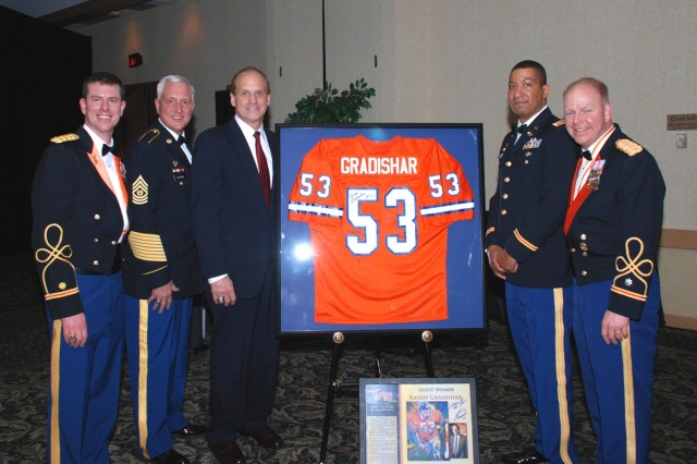 """Signalers of the 53rd Signal Battalion share the spotlight with their new """"Patron Saint"""" No. 53 Randy Gradishar (center), formally with the Denver Broncos. From left to right are Maj. Stephen Wellein, Command Sgt. Maj. Timothy Czuba, Gradishar, Maj. Sam Patton and Lt. Col. Patrick Kerr, commander."""