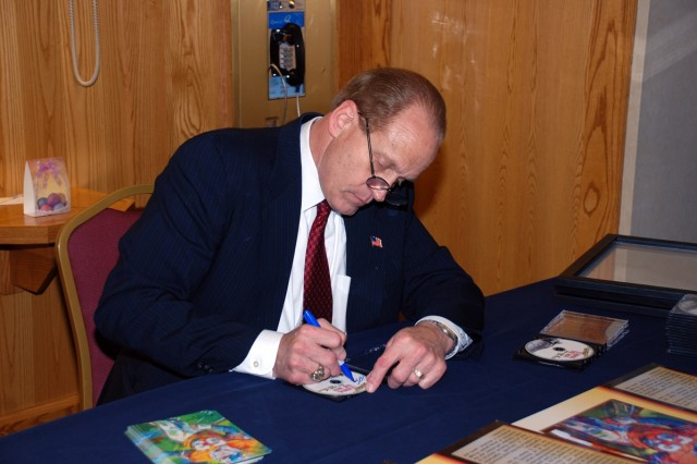 The Champion of Champion, Ohio, former NFL great Randy Gradishar, spends a few moments autographing memorabilia prior to the 2009 USASMDC/ARSTRAT Ball festivities.