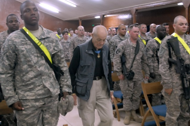 Soldiers serving with the 2nd Heavy Brigade Combat Team, 1st Infantry Division, Multi-National Division - Baghdad, stand at the position of attention while Col. (retired) Robert Howard (center) and Command Sgt. Maj. (retired) Gary Littrell arrive at the Warrior Chapel on Camp Liberty, April 14. The two retired Vietnam War veterans, who earned the Medal of Honor while in combat, spoke words of encouragement to the Soldiers and answered their questions.