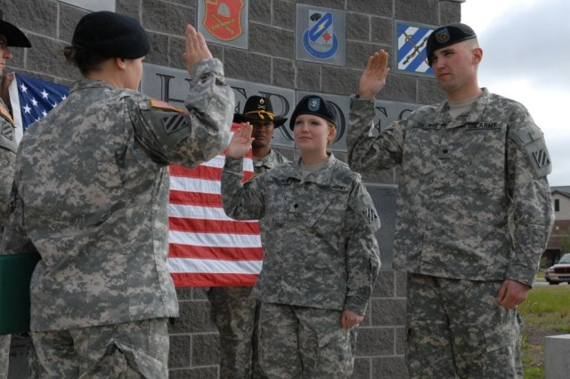 Captain Joan Hollien, the commander of Headquarters and Headquarters Troop, 3rd Heavy Brigade Combat Team, 3rd Infantry Division, recites the oath of  reenlistment to Spc. Bradley Tollberg, a scout in the 3rd Squadron, 1st Cavalry Regiment, 3rd HBCT and his wife Spc. Sadie Tollberg, the nuclear, biological and chemical clerk for HHT, BSTB, during a reenlistment ceremony beside the 3rd HBCT's headquarters at Kelley Hill, on Fort Benning, Ga., April 9. The couple reenlisted to stay at Fort Benning four more years