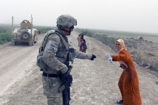 A Soldier assigned to 5th Battalion, 82nd Field Artillery Regiment, 4th Brigade Combat Team, 1st Cavalry Division, delivers a flyer to an Iraqi woman during a joint patrol with Iraqi Army Soldiers April 2. The flyer contains contact information for citizens to report on criminal activities.