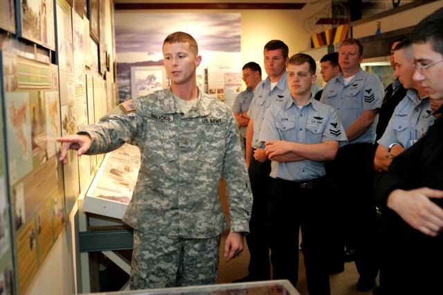 Explaining the history of the unmovable Rock of the Marne and its' tradition, 2nd Lt. Robert Brooks describes the story to Sailors from USS Georgia at the Fort Stewart Museum April 8.