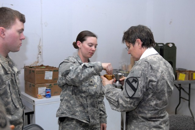 BAGHDAD - Chaplain (Lt. Col.) Barbara Sherer administers communion to Sgt. Sheena Barnett of the 492nd Civil Affairs Battalion, at Joint Security Station Hope on Easter Sunday evening. Assigned to the 3rd Brigade Combat Team, 82nd  Airborne Division, Sgt. Barnett is one of many grateful Soldiers the MND-B chaplains reached on a four station trip.