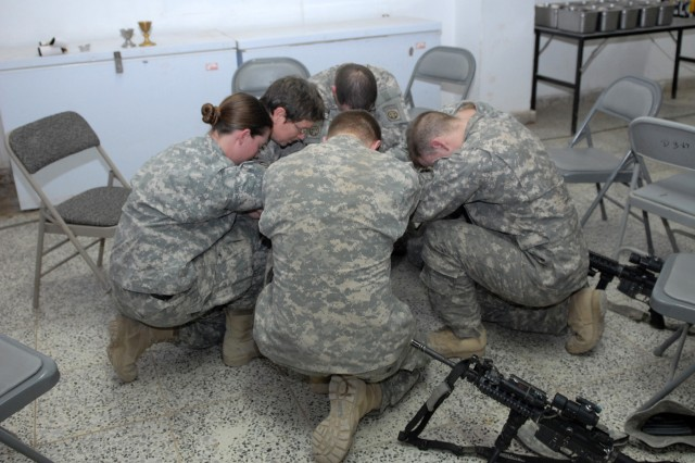 "BAGHDAD - Soldiers of Company B, 2nd Battalion, 505th Parachute Infantry Regiment at Joint Security Station Hope gather in prayer with Chaplain (Lt. Col.) Barbara Sherer after receiving Easter communion. JSS Hope was the last of four stations two MND-B chaplains visited in order to conduct Easter services to troops without fulltime chaplain support. Although the entire trip traversed Baghdad twice and lasted approximately 16 hours, Chaplain Sherer was more than happy to visit each relatively remote station. ""On Easter Sunday, where else would I be? There is no where else I'd rather be than out here with the Soldiers."""