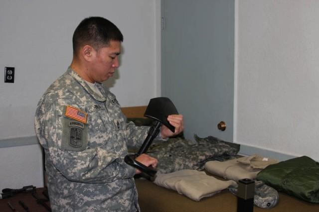 Sgt. 1st Class Keith Hiura, a Warrior Leader Course instructor at U.S. Army Alaska\'s Sgt. 1st Class Christopher R. Brevard NCO Academy, Fort Richardson, inspects an entrenching tool during the Commandant's Inspection .