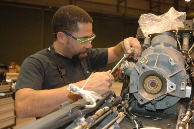 MANNHEIM, Germany -- Dyncorp International employee Richard Clark tightens a bolt on a UH-60 Black Hawk tail rotor intermediate gear box.