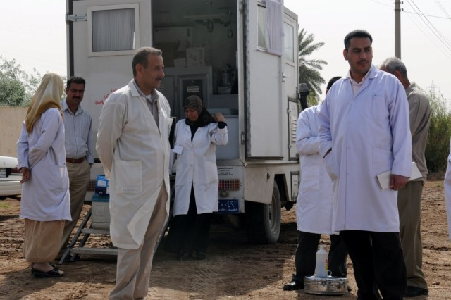 BAGHDAD - Staff from the Lutifiyah Public Health Center stand in front of their mobile medical clinic vehicle at Kinana School, April 8. The vehicle contains medical equipment and supplies to treat the patients from the local community who were seen that day by the medical staff of the Lutifiyah Public Health Center.