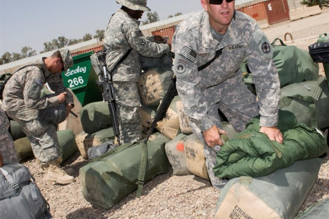 Soldiers of the 154th Transportation Company make last-minute adjustments to their bags prior to leaving for Afghanistan at Baghdad International Airport, Iraq, April 14. The 154th Trans. Co., an active-component unit from Fort Hood, Texas, is the second 3rd Sustainment Command (Expeditionary) unit in three weeks to move directly to Afghanistan from Iraq.
