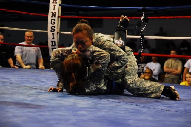 Sgt. Francine Carriaga (top) battles Pfc. Shelly Najera during middleweight Army Combatives tournament action at Osan Air Base, April 4.