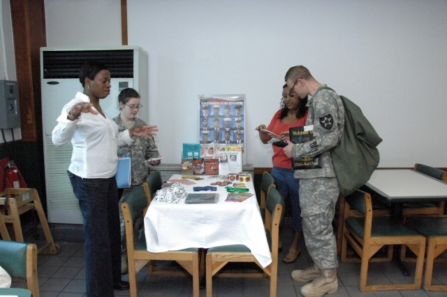 Joann Taalib (left), ACS family advocacy program specialist, explains the ACS literature to Pvt. Beth Ipsen (right of Taalib) while Claudia Figuroa (right rear) shows family advocacy material to Pfc. Gregory Good during the Month of the Military Child celebration in the USAG-RC Food Court, April 10.