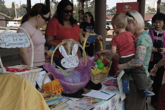 Parents and children of the USAG-Red Cloud community enjoy prizes and Easter eggs provided by BOSS, ACS, Red Cloud commissary, and AAFES during the annual FMWR Pear Blossom Cottage Easter Egg hunt held on the Village Green on USAG- Red Cloud April 10.