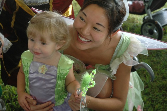 SCHOFIELD BARRACKS, Hawaii - Abygail Starke, 2, poses for a photograph with Tinkerbell during Breakfast with Disney, a special Month of the Military Child event at Sills Field, April 11. Fifteen Disney characters created a magical morning for more than 350 children and parents.