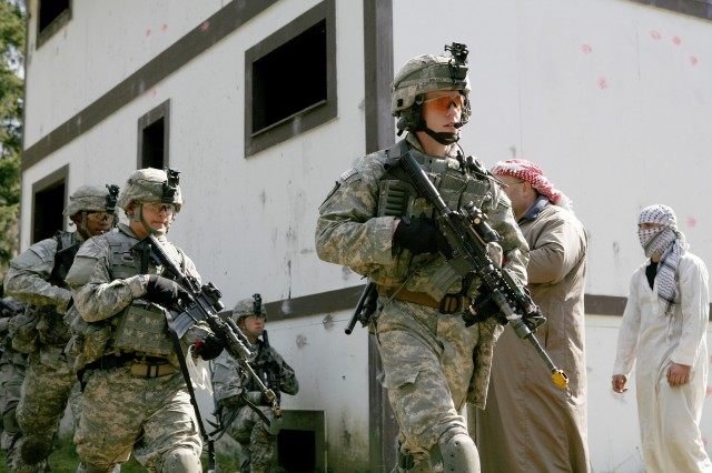 Sgt. Nathan Wilkes, Pvt. Steven Pilotzi and Pvt. Darren Hemingway (right to left) walk past simulated Iraqi villagers during a leader engagement exercise.
