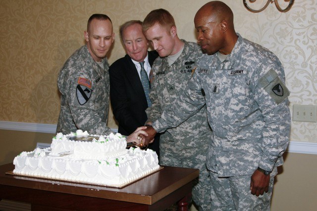 PICATINNY ARSENAL, N.J. - Command Sgt. Maj. Rodney Rhoades (from left), U.S. Rep. Rodney P. Frelinghuysen, Cpl. Sean Brennan and Command Sgt. Maj. Larry Taylor participate in a time-honored tradition by using an NCO sword to cut a cake at a reception here April 4. It is tradition for the youngest and oldest Soldiers to cut the cake and serve the first pieces. Rhoades announced that Brennan was the youngest Soldier in the room, but that it was up to the audience to use their imaginations to determine the oldest.