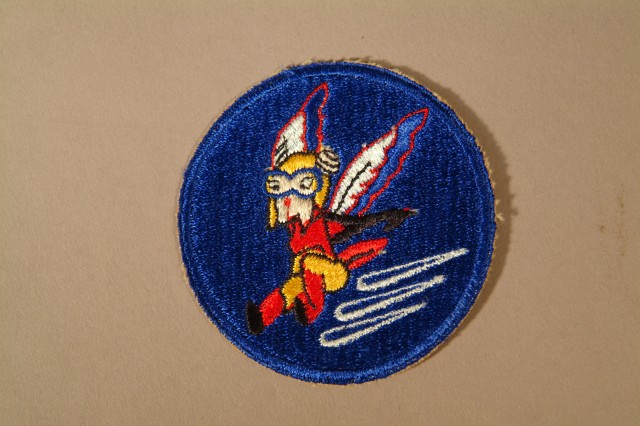 """Shoulder Sleeve insignia of the Womens Auxiliary Ferrying Squadron. The patch depicts the Walt Disney Studios designed """"Fifinella,"""" coming in for a landing.  """"Fifinella"""" was a winged female gremlin in a red and yellow suit with red high top boots and black gloves.  According to Barry Stein, her mission was to seek and destroy male gremlins, which were believed to cause all types of aircraft malfunctions, including those by the aircrew.  The WAFS were tasked with ferrying all types of Army Air Force aircraft from the factories to the military air fields throughout the country.  In doing so, they freed up male pilots who were needed in combat theaters.  Before the end of World War II, the WAFS were incorporated into the organization Womens Air Force Service Pilots, or WASPs.(Army Heritage Museum)."""