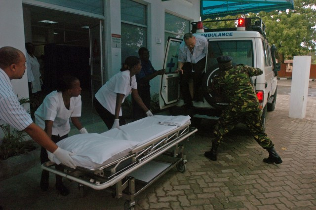 """Capt. Jonathan Ji, U.S. Army Central field surgeon, jumps out of an ambulance as the staff of Aga Khan Hospital prepare to receive a """"patient"""" during a joint medical-evacuation exercise held with the Kenyan and U.S. Army, in Mombasa, Kenya,"""