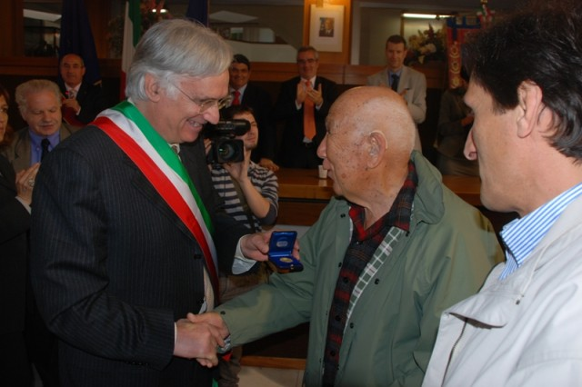 The mayor of Massa, Dr. Roberto Pucci, presents Noel Okamoto with a medal as a token of appreciation for the liberation of Massa by Japanese American Soldiers assigned to the 442nd 442nd Regimental Combat Team. April 10, 2009 the town of Massa celebrated the 64th anniversary of the liberation of their town.