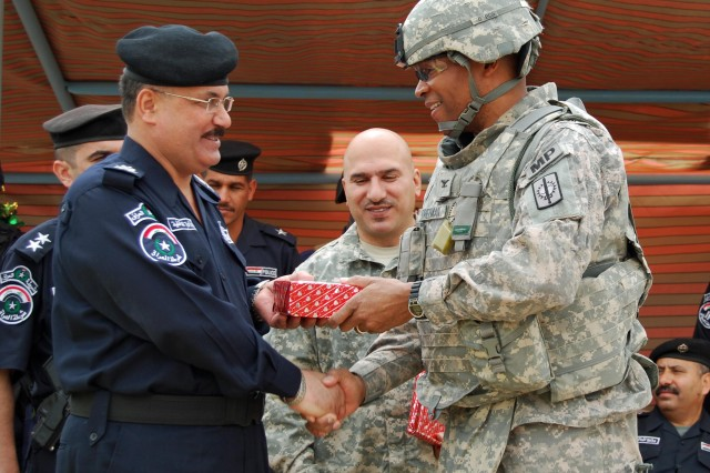 BAGHDAD- Maj. Gen. Ali Adnan Yunis (left), director, Provincial Directorate of Police, presents Col. Byron Freeman, commander, 8th Military Police Brigade, and a native of Norfolk, Va., with a token of appreciation for the excellent mission the Soldiers of the 8th MP Bde. have performed in mentoring, coaching and teaching the Iraqi Police, both new recruits and senior officers.  The presentation was a highlight of graduation ceremonies at the Al Furat Iraqi Police Training Center, April 15.