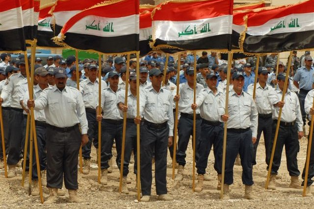 BAGHDAD- New graduates of the Al Furat Iraqi Police Training Center proudly drill as the Iraqi flags they hold flutter in the breeze. 537 Iraqi Police recruits graduated April 15.