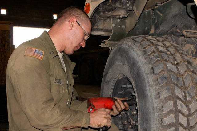 """Camp Taji, Iraq - Kokomo, Ind. native Pfc. Wayne Bogard, light wheel mechanic for Company B, 115th """"Muleskinners"""" Brigade Support Battalion tightens the bolts after changing and rotating the tires on a humvee here April 17."""