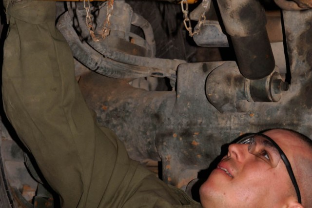 """Camp Taji, Iraq - Austin, Texas native, Spc. Philip Thompson, light-wheel mechanic for Company B, 115th """"Muleskinners"""" Brigade Support Battalion, checks for leaks April 17 here on a Palletized Load System vehicle to ensure proper performance for a future mission."""
